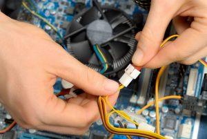Die Hände eines Elektrotechnikers beim Reparieren oder Einbauen von Computerteilen